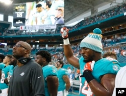 Miami Dolphins defensive end Robert Quinn raises his right fist during the singing of the National Anthem, before the start of an NFL preseason football game against the Tampa Bay Buccaneers, Aug. 9, 2018 in Miami Gardens, Fla.