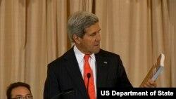 美国国务卿克里在发布会上手持《2014年世界人口走私状况报告》(2014年6月20日, 美国国务院视频截图)