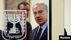 FILE - Israeli Prime Minister Benjamin Netanyahu is seen through a glass door in Jerusalem Oct. 7, 2013.