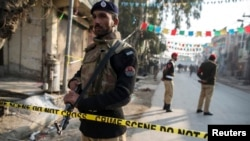 A policemen cordons off the site of a suicide blast in Rawalpini, Pakistan, Jan. 20, 2014.