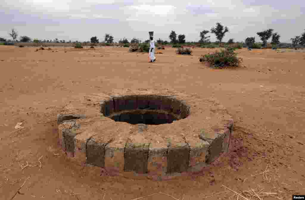 A woman walks past the well, where the bodies of suspected Islamist rebels, director of Human Rights Watch, Philippe Bolopion, had been dumped, according to U.N., in Sevare, Mali. Rights groups are worried ethnic reprisals will spread as parts of the north are retaken by Malian and French troops.