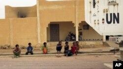 Des enfants contemplent un véhicule de la mission de l'ONU au Mali, la MINUSMA, dans une rue de Kidal, le 23 juillet 2015.