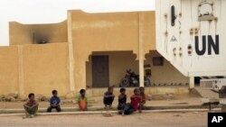 FILE - Children watch as a MINUSMA peacekeeping armored vehicle drives past in Kidal, Mali, July 23, 2015.