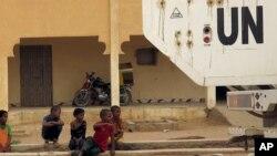Des enfants assis sur une rue à côté d'un véhicule de l'ONU qui passe à Kidal, Mali, 23 juillet 2015.