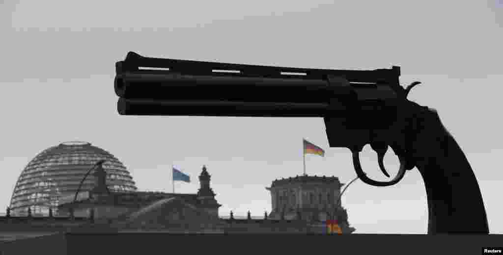 "A sculpture showing a pistol, inspired by Swedish artist Carl Frederik Reutersvaerd sculpture's ""Non-Violence"", is pictured in front of the Reichstag building in Berlin, Germany."