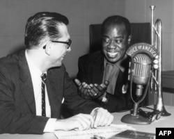 FILE - VOA jazz broadcaster Willis Conover interviews the legendary Louis Armstrong.