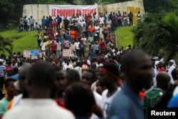Supporters of Ivory Coast's opposition hold placards as they protest during a political rally ahead of the referendum on a new constitution, in Abidjan, Ivory Coast, Oct. 28, 2016.