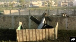 This photo, taken by a local resident, shows the wreckage of a helicopter next to the wall of the compound where according to officials, Osama bin Laden was shot and killed in a firefight with U.S. forces in Abbottabad, Pakistan, May 2, 2011 (file photo)