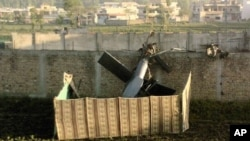 In this May 2, 2011 file photo, taken by a local resident, shows the wreckage of a helicopter next to the wall of the compound where according to officials, Osama bin Laden was shot and killed in a firefight with U.S. forces in Abbottabad, Pakistan.
