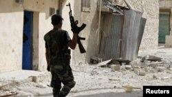 ທະຫານກະບົດ ຊີເຣຍ ຄົນນຶ່ງ ກໍາລັງຢ່າງຜ່ານຊາກຫັກພັງຂອງເມືອງ Aleppo.