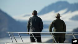 President Barack Obama, accompanied by a National Park Service employee looks at Bear Glacier, which has receded 1.8 miles in approximately 100 years, while on a boat tour to see the effects of global warming in Resurrection Cove, Sept. 1, 2015, in Seward