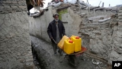 FILE - An Afghan man uses a wheelbarrow to move containers of water in Kabul, Feb. 12, 2018.