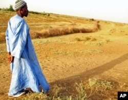 FILE - A farmer in Senegal walks across parched land which used to be a riverbed.