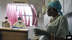 Pinky Molefe (R) gets TB medication at a clinic in Alexandra township north of Johannesburg, South Africa, Oct. 13, 2010 (file photo)
