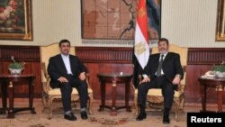 Presiden Mesir Mohamed Morsi (kanan), dan Presiden Iran Mahmoud Ahmadinejad setibanya di bandara Internasional di Kairo (5/2).