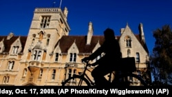 A cyclist is silhouetted in front of Balliol College, founded in 1263. It is one of the oldest colleges of Oxford University in Oxford, England, Friday, Oct. 17, 2008. (AP Photo/Kirsty Wigglesworth)