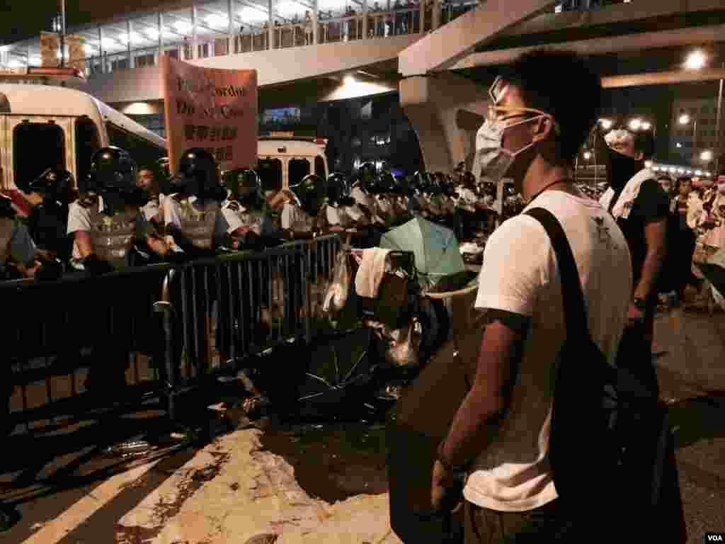 星期一午夜12時後,仍有大量示威者聚集在香港政府總部對開的馬路,與戴上防毒面具的防暴警察對峙。(美國之音湯惠芸拍攝)
