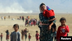 FILE - Displaced Yazidis, fleeing from Islamic State militants, are seen heading toward the Syrian border Aug. 11, 2014.