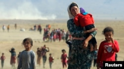 FILE - Displaced Iraqi Yazidis, fleeing from Islamic State militants, head toward the Syrian border Aug. 11, 2014. The Obama administration must determine whether the IS group has been conducting a genocide campaign.