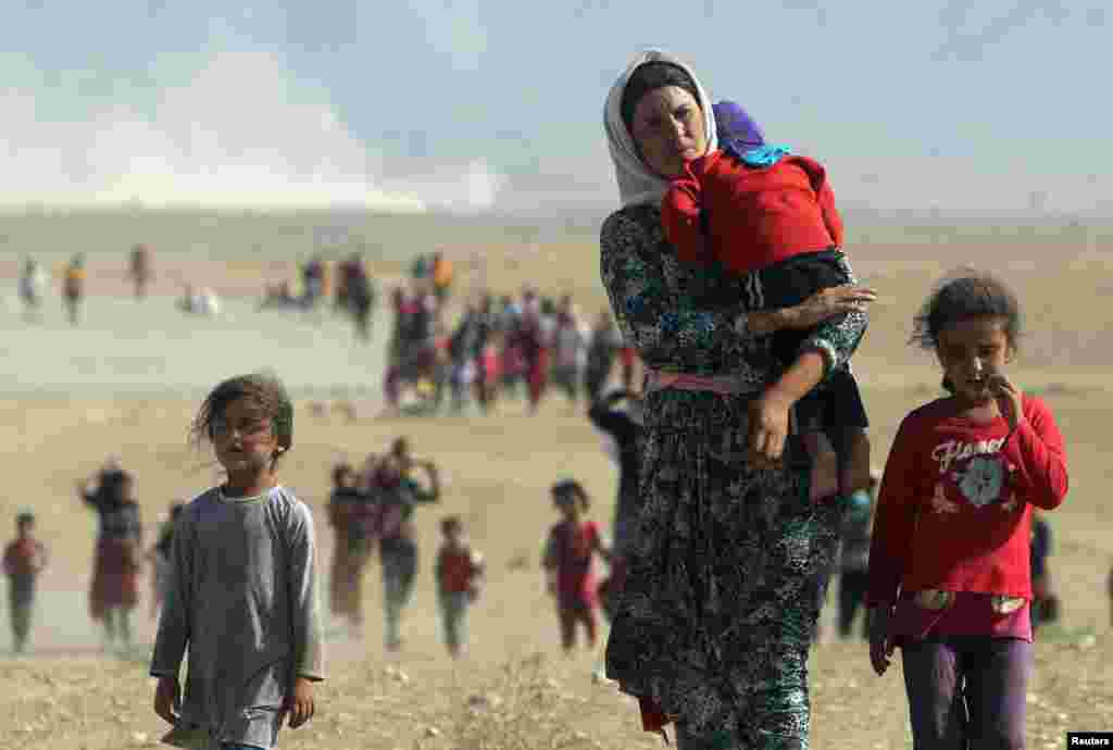 Displaced Yazidis, fleeing violence from forces loyal to the Islamic State group, head toward the Syrian border on the outskirts of Sinjar mountain, near the Syrian border town of Elierbeh of Al-Hasakah Governorate, Aug. 11, 2014.