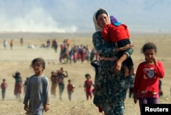 FILE - Displaced Yazidis, fleeing violence from forces loyal to the Islamic State group, head toward the Syrian border Aug. 11, 2014.