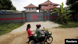 Women ride a motorcycle past a house that is used to temporarily house asylum seekers sent from a Nauru detention center in Phnom Penh, Cambodia, Aug. 31, 2015.