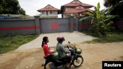 Women ride a motorcycle past a house in Phnom Penh, Cambodia, that is used to temporarily house asylum seekers sent from a Nauru detention center, Aug. 31, 2015.