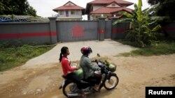 Phụ nữ lái xe máy qua một ngôi nhà tại Phnom Penh, Campuchia, được sử dụng để tạm giam người tị nạn được gửi đến từ trung tâm giam giữ Nauru.