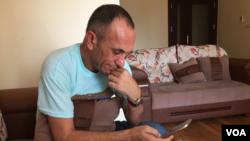 Yazidi activist, Khaleel al-Dakhi, using his cellphone to track down Yazidi women captured by Islamic State extremists. (Sharon Behn/VOA)