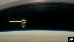 "FILE - This image made available by NASA in April 2017 shows a still from the short film ""Cassini's Grand Finale,"" with the spacecraft diving between Saturn and the planet's innermost ring."