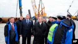 Russian President Vladimir Putin (S) visits the construction site of the Kerch Strait bridge on Tuzla Island, Crimea, March 18, 2016. Putin traveled to Crimea to mark the second anniversary of the peninsula's seizure from Ukraine.