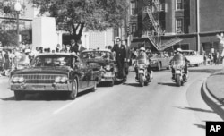 FILE - Seen through the limousine's windshield as it proceeds along Elm Street past the Texas School Book Depository, President John F. Kennedy appears to raise his hand toward his head within seconds of being fatally shot in Dallas, Nov 22, 1963.