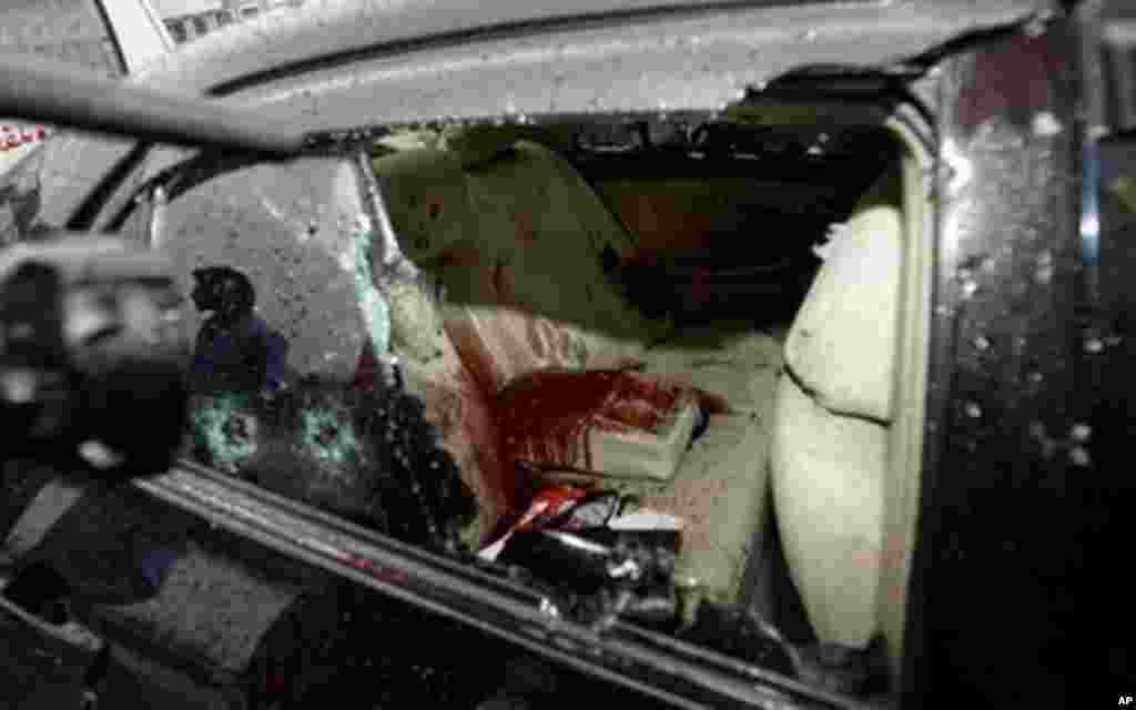 A Pakistani cameraman films the blood-stained car of slain Pakistan's government minister Shahbaz Bhatti in Islamabad, Pakistan, March 2, 2011.
