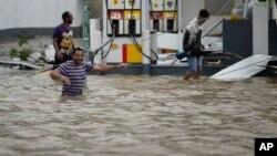Người dân lội qua khu vực ngập lụt do bão Maria gây ra gần 1 trạm xăng trên đảo Puerto Rico hôm 20/9.