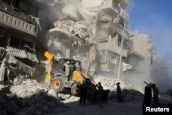A front loader removes debris at a damaged site after airstrikes on the rebel held Tariq al-Bab neighborhood of Aleppo, Syria, Sept. 24, 2016.