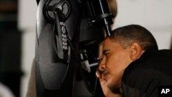El presidente Barack Obama mirando por un telescopio durante el primer evento astronómico en el jardín sur de la Casa Blanca, en 2009.