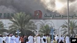 Omani nationals watch smoke rise from Lulu hypermarket in Sohar, February 28, 2011