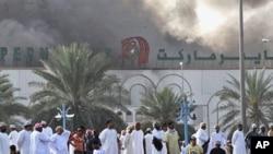 Omani nationals watch smoke rise from Lulu hypermarket in Sohar, February 28, 2011