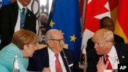Presiden Amerika Serikat Donald Trump (kanan) dan Kanselir Jerman Angela Merkel (kiri) berbicara dengan Presiden Tunisia Beji Caid Essebsi (tengah) saat menghadiri pertemuan meja bundar pemimpin G7 di Hotel San Domenico di Taormina, Italia, 27 Mei 2017.