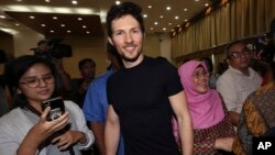 Telegram co-founder Pavel Durov, center, smiles as he leaves after a press conference following his meeting with Indonesian Communication and Information Minister Rudiantara in Jakarta, Indonesia, Aug. 1, 2017.