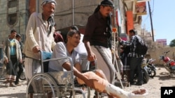 In this Nov. 23, 2015 photo, wounded people gather during a protest demanding treatment and an end to the blockade imposed by Shiite fighters, known as Houthis, in Taiz, Yemen's third largest city.