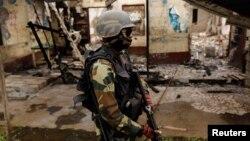 Un membre du bataillon camerounais d'élite d'intervention rapide (BIR) patrouille dans le village abandonné d'Elona, près de Buea, dans la région anglophone du sud-ouest du Cameroun, le 4 octobre 2018.