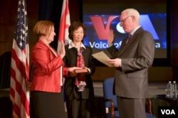 美国之音新台长阿曼达·贝内特(Amanda Bennett,左)一手放在家传的圣经上宣誓就职(2016年4月18日)