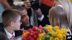 """Barack Obama conversa con dos niños durante la comida """"Kids State Dinner"""" en la Casa Blanca."""
