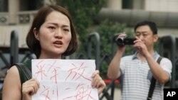 Li Wenzu, istri pengacara HAM China yang sedang dipenjara, Wang Quanzhang, memegang kertas bertuliskan permintaan pembebasan para pengacara, di Tianjin, China. (Foto: Dok)
