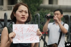 "FILE - Li Wenzu, wife of imprisoned lawyer Wang Quanzhang, holds a paper that reads ""Release Liu Ermin"" as she and supporters of a prominent Chinese human rights lawyer stage a protest outside the Tianjin No. 2 Intermediate People's Court in Tianjin, China, Aug. 1, 2016."
