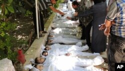 ພົນລະເຮືອນຊີເຣຍ ກໍາລັງກວດເບິ່ງວ່າສົບໃດແມ່ນຂອງໃຜ ລຸນຫລັງ ການໂຈມຕີຂອງທະຫານລັດຖະບານ ທີ່ຖືກກ່າວຫາວ່າ ໃຊ້ອາຍແກັສເປັນພິດ ໃນນະຄອນ Damascus ໃນວັນທີ 21 ສິງຫາ 2013.