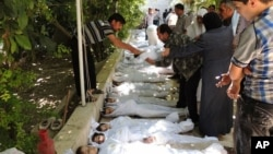 A citizen journalism image provided by the Local Committee of Arbeen which has been authenticated based on contents and AP reporting, shows Syrian citizens trying to identify dead bodies, after an alleged poison gas attack by government forces. There has