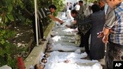 Civilë sirianë përpiqen të identifikojnë trupat e të afërmve. Fotoja është marrë nga një banor, ofruar nga Komisioni Lokal Arbeen. Vërtetësia e fotos është konfirmuar nga materiale të agjencisë së lajmeve Associated Press.