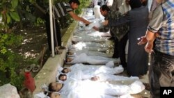 Syrian citizens trying to identify dead bodies, after an alleged poison gas attack by government forces.